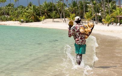 shutterstock_226837327-SANTO-DOMINGO---DOMINICAN-REPUBLIC-A-coconut-saler-walking-by-the-sea-in-the-famous-Juan-Dolio-Beach-with-the-atmospheric-background-of-palm-trees
