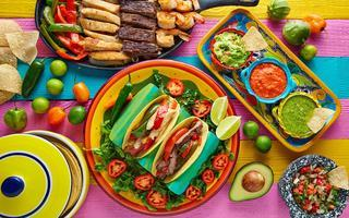 shutterstock_423022273-Mexican-chicken-and-beef-fajitas-tacos-in-colorful-table
