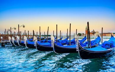 shutterstock_148843169-Venice_-gondolas-or-gondole-on-a-blue-sunset-twilight-and-San-Giorgio-Maggiore-church-landmark-on-background.-Italy_-Europe