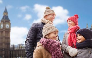 shutterstock_552005083-family_-travel_-tourism_-winter-holidays-and-people-concept---happy-parents-with-kids-over-london-city-background